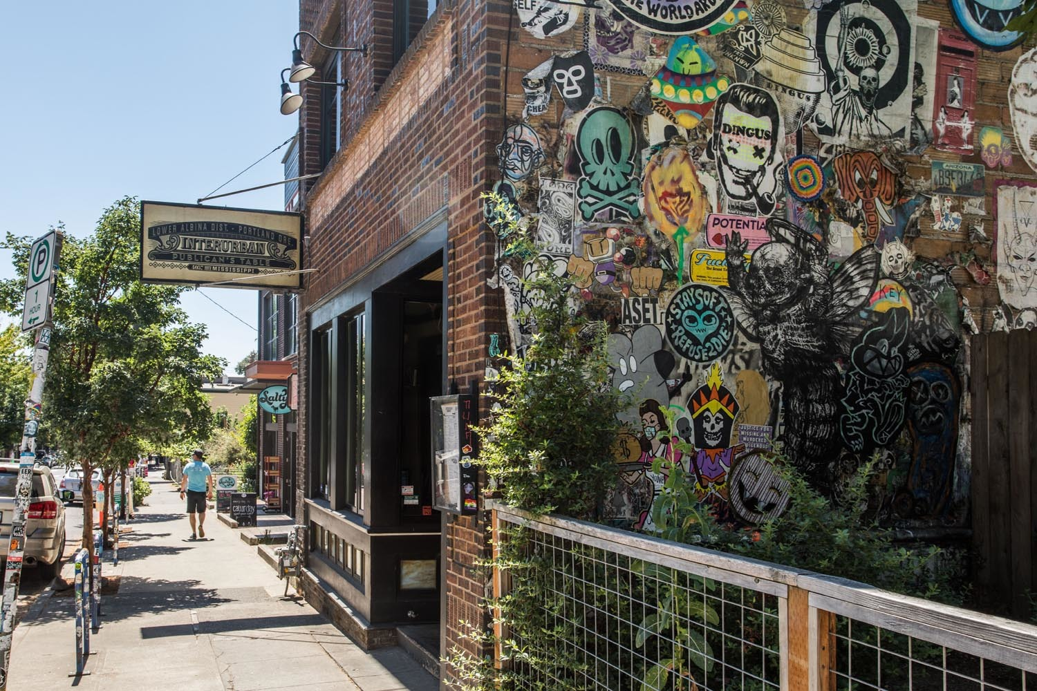 brick building exterior with street art and trees