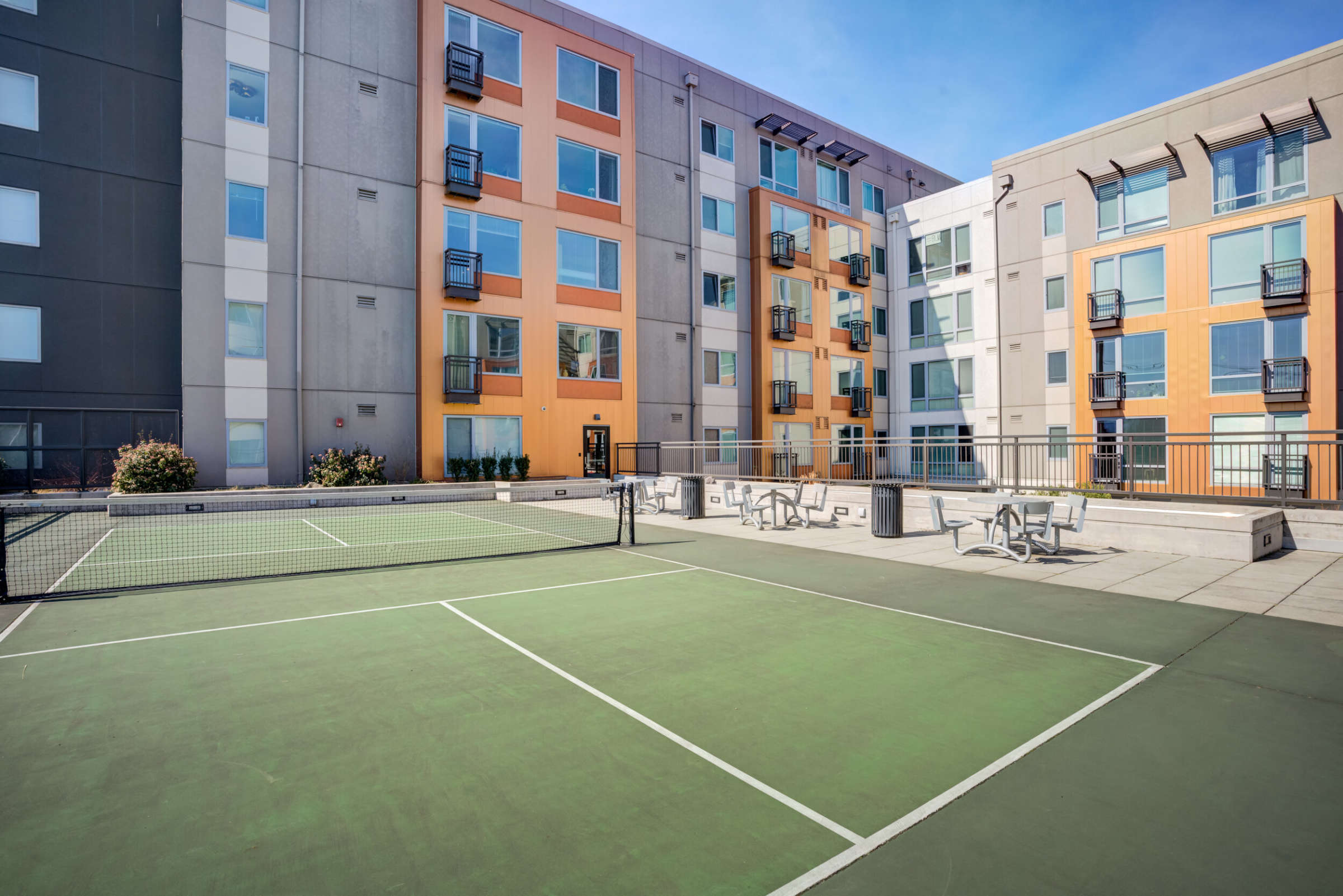 Apartment building exterior and view of pickle ball court